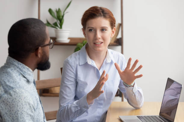 Two diverse businesspeople chatting sitting behind laptop in office. Excited female sharing ideas or startup business plan with male coworker. Informal conversation, work break concept
